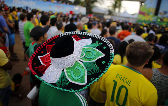 A Mexican fan wears a traditional hat as he watches a 2014 World Cup soccer match at the fan fest area in Natal