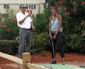U.S. President Obama and first lady Michelle Obama react during a round of putt putt golf in Panama City Beach
