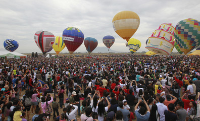 People watch and take pictures as hot air balloons prepare to take off during the annual Hot Air Balloon festival at Clark airbase, a former U.S. base in Angeles city