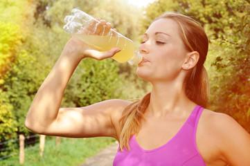Frau bei Laufen, Sport und Jogging trinkt isotonisches Getränk