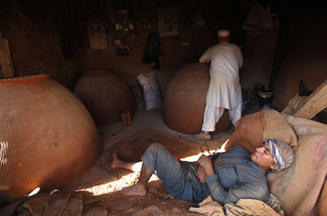 An Afghan man sleeps while another makes a tandoor oven used for making bread in Kabul