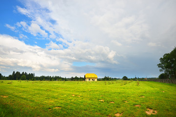 Modern farm house in a green field on a summer day