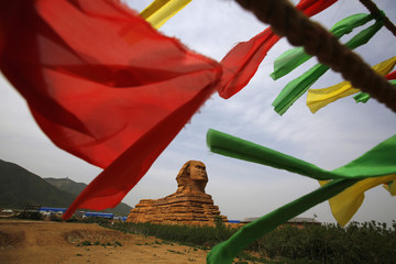 A full-scale replica of the Sphinx, which is part of an unfinished theme park that will also accommodate the production of movies, television shows and animation, is seen behind coloured flags on the outskirts of Shijiazhuang