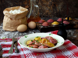 Fresh pink yellow beet dumplings or ravioli stuffed with ricotta cheese with butter sauce on wooden board on dark background. Space for text