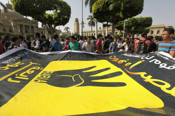 Cairo university students and members of the Muslim Brotherhood carry a banner with symbol of Rabaa during protest against military in Cairo