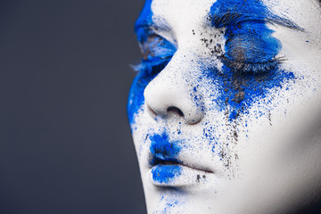 fashion model girl portrait with colorful powder make up. woman with bright blue makeup and white skin. Abstract fantasy make-up