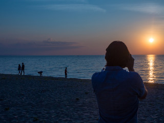 Man Taking Picture at Sunset on Beach