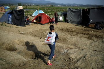 A boy carries a bag with bottles of water at a makeshift camp for migrants and refugees at the Greek-Macedonian border near the village of Idomeni