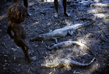 Johnny, the three-year-old grandson of Australian Aboriginal hunter Roy Gaykamangu looks at the crocodiles and a native Australian lizard called a Goanna that have been killed at a billabong in East Arnhem Land