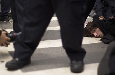 New York Police Department officers hold Occupy Wall Street activist on ground as he is detained during a march through streets of Manhattan in New York