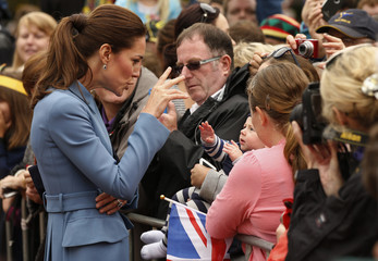 Catherine, Duchess of Cambridge, reacts as she meets a baby in the crowd after laying a wreath with her husband, Britain's Prince William, at the war memorial in Seymour Square