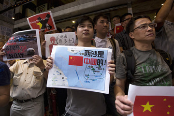 Anti-Vietnam protesters hold posters and a picture showing a map of the South China Sea including the Paracel Islands, during a protest defending China's territory claim and condemning Vietnam's anti-Chinese protests, in Hong Kong