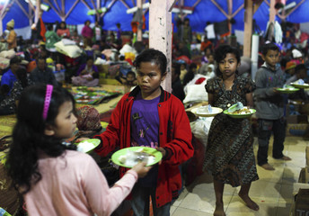 Youths hold plates of dinner to be served to villagers evacuated from their homes due to Mount Sinabung's eruption, at a temporary shelter in Brastagi