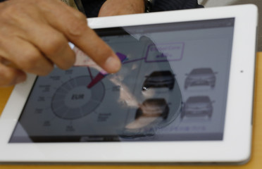 Toyota Motor Corp's Managing Officer Fukuichi is reflected on an iPad as he shows images of various car designs during an interview with Reuters at the company's design center building in Toyota, central Japan
