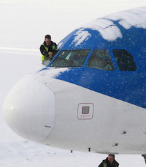 An engineer tries to clear snow from the windscreen of an aeroplane at Edinburgh Airport, in Edinburgh