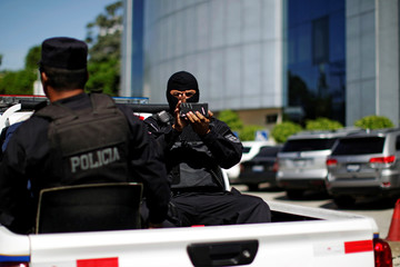 A policemen uses a mobile phone during a protest of relatives of imprisoned Barrio 18 gang members asking for less severe measures in prisons in San Salvador