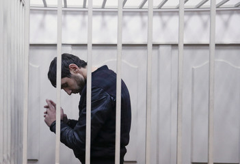 Zaur Dadayev, charged over the killing of Russian opposition figure Boris Nemtsov, stands inside a defendants' cage at a court building in Moscow