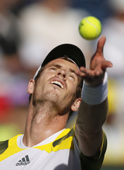 Murray of Britain tosses the ball to serve against Potro of Argentina during their men's singles quarterfinal match at the BNP Paribas Open ATP tennis tournament in Indian Wells