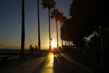 seaside boulevard in Marbella, Spain with colorful lens flares during sunset