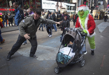 """Man dressed up as """"the Grinch"""", a fictional character by author Dr. Seuss, who poses for photos with people for money, poses for a picture with a baby in a stroller and his father in Times Square during Black Friday"""