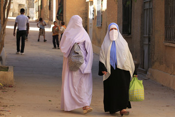 Women wearing traditional dresses walk at the old city of Boussaada