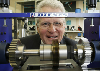Supe-Dienes director of German industrial knife manufacturer Dienes poses for a picture behind an industrial knife model at the workshop of his company in Overath