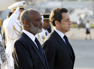 France's President Sarkozy and Haitian President Preval stand at attention upon arrival at Toussaint Louverture Airport in Port-au-Prince