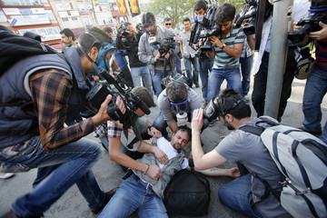 An injured journalist is filmed and helped by his colleagues during clashes between riot police and May Day protesters in central Istanbul