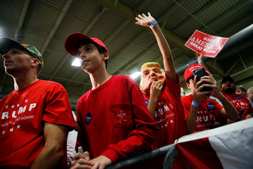 A boy wears a Trump mask and tries to get Trump's attention onstage as supporters rally with the candidate in Fletcher, North Carolina