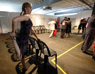 A contestant warms up as other competitors rehearse backstage during the Salon Tango style qualifier round at the 10th edition of the Tango World Championship in Buenos Aires