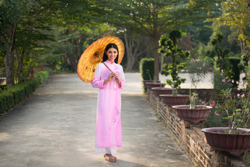 asia beautiful woman with umbrella in Vietnam dress traditional.