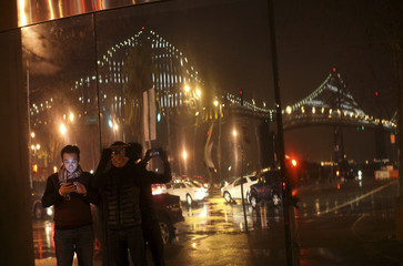 People photograph a lighted art display of the San Francisco-Oakland Bay Bridge as it is reflected in a window, in San Francisco