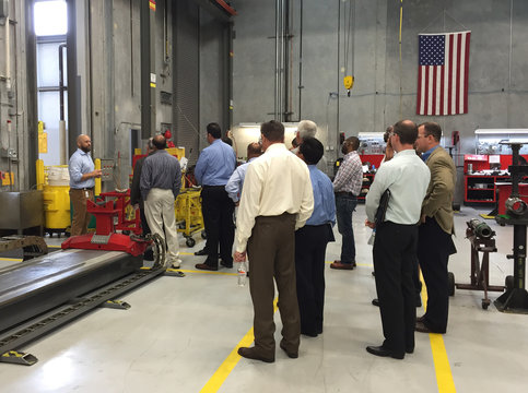 John O?Hara, business development manager for Halliburton Co, describes a piece of equipment to members of Pay-It-Forward During The Downturn, a networking group for laid-off white collar oilfield workers, during a tour of a Halliburton facility in Spring