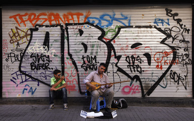 A street musician plays the saz, a traditional musical instrument, as a man takes pictures, in Istanbul