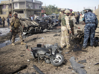 Iraqi security forces personnel examine the remains of a car bomb in Baghdad