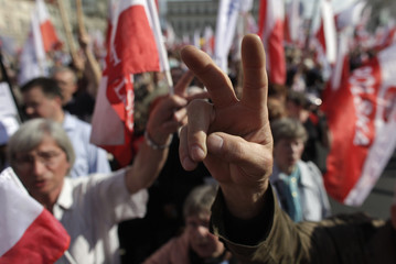 People gesture victory signs as they take part in a march at Three Crosses Square in Warsaw