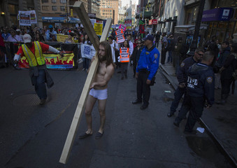 A man carries a cross while taking part in a May Day march through downtown Manhattan, New York