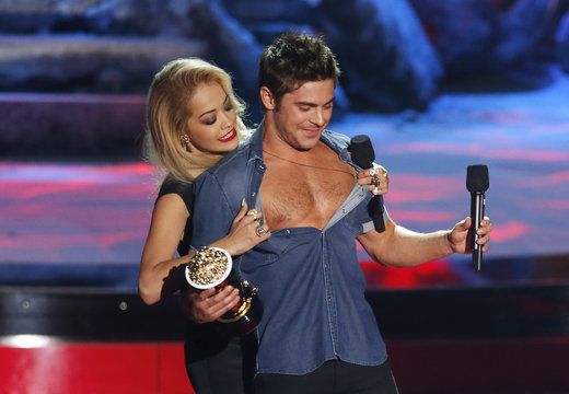 """Zac Efron accepts the award for best shirtless performance for """"That Awkward Moment"""" as his shirt is ripped open by presenter Rita Ora at the 2014 MTV Movie Awards in Los Angeles"""