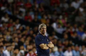 Manchester City team manager Pellegrini looks on during their soccer match against South China at the Barclays Asia Trophy friendly tournament in Hong Kong