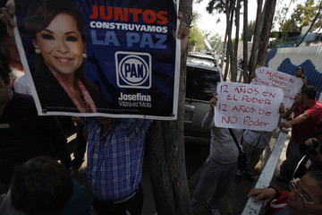 Supporter of Vazquez Mota, presidential candidate of the PAN, holds up a poster as men protest against her party outside an elementary school in Mexico City