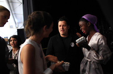 Designer Isaac Mizrahi talks with models backstage before his Spring 2011 collection during New York Fashion Week
