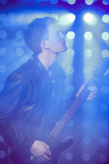 young rock musician playing electric guitar and singing. Rock star on background of spotlights