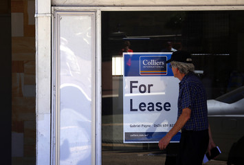 """A man looks at a """"For Lease"""" sign displayed in the window of a vacant shop in the Western Australian capital city of Perth"""