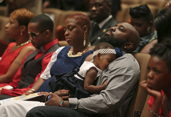 Michael Brown Sr. sits with an unidentified girl on his lap during funeral service for his son, Michael Brown, at Friendly Temple Missionary Baptist Church in St. Louis