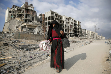 A Palestinian woman walks past destroyed buildings in the town of Beit Lahiya in the northern Gaza Strip