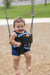 8 Month Old Baby Boy On Swing At A Playground