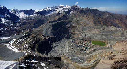 An aerial view of open pits of CODELCO's Andina and Anglo American's Los Bronces copper mines with Olivares glaciers in the background at Los Andes Mountain range