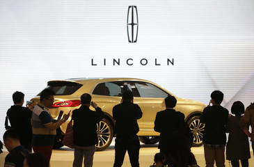 Visitors take photos of a Lincoln MKX SUV concept car at Auto China 2014 in Beijing