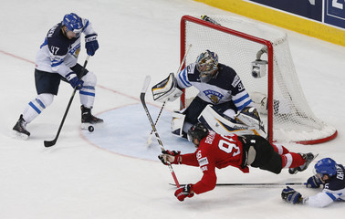 Switzerland's Brunner (bottm) falls as he tries to score against Finland's Lajunen and goalie Rinne during overtime of their men's ice hockey World Championship Group B game at Minsk Arena in Minsk