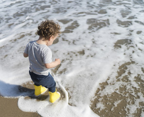 Toddler playing near the surf  of the Pacific Ocean.